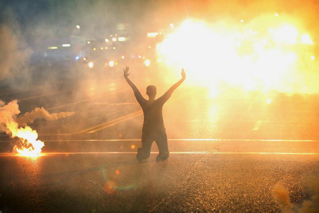 Protest-Ferguson-man-kneeling-surrounded-by-smoke